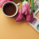 Creative flat lay of coffee cup, watercolor palette and bouquet of pink tulips. Artist workplace on a pale peach pastel background royalty free stock photography