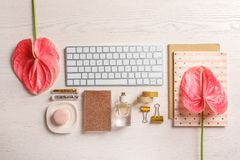 Creative flat lay composition with tropical flowers and computer keyboard. On wooden background royalty free stock photo