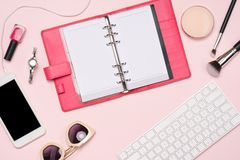 Creative flat lay photo of workspace with cosmetics, coffee, smartphone, glasses,mascara,gloss with copy space on pink background royalty free stock photos