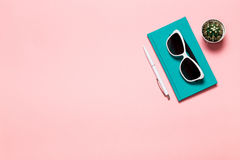 Creative flat lay photo of workspace desk with aquamarine notebook, eyeglasses, cactus with copy space pink background. Minimal style Stock Images