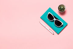 Creative flat lay photo of workspace desk with aquamarine notebook, eyeglasses, cactus copy space pink background stock photography