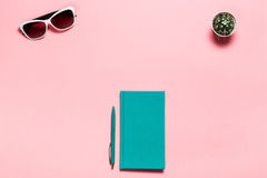 Creative flat lay photo of workspace desk with aquamarine notebook, eyeglasses, cactus copy space pink background royalty free stock photography