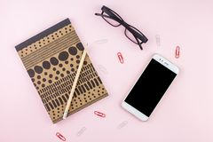 Creative flat lay photo of workspace desk with smartphone, eyeglasses, pen, pencil and notebook, minimal style on pink background. Minimal business concept Royalty Free Stock Photography