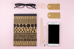 Creative flat lay photo of workspace desk with smartphone, eyeglasses, pen, pencil and notebook, minimal style on pink background. Minimal business concept Stock Image