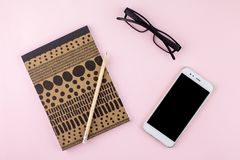 Creative flat lay photo of workspace desk with smartphone, eyeglasses, pen, pencil and notebook, minimal style on pink background. Minimal business concept Stock Photography