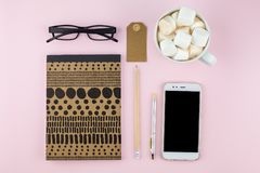 Creative flat lay photo of workspace desk with smartphone, eyeglasses, pen, pencil and notebook, minimal style on pink background. Minimal business concept Stock Images