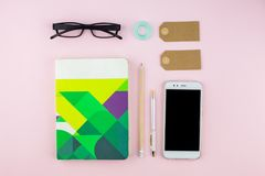 Creative flat lay photo of workspace desk with smartphone, eyeglasses, pen, pencil and notebook, minimal style on pink background. Minimal business concept Stock Photo