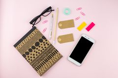 Creative flat lay photo of workspace desk with smartphone, eyeglasses, pen, pencil and notebook, minimal style on pink background. Minimal business concept Royalty Free Stock Photo