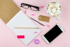 Creative flat lay photo of workspace desk with smartphone, eyeglasses, pen, pencil and notebook, minimal style on pink background. Minimal business concept Royalty Free Stock Image