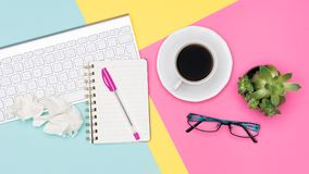 Top view office desk with notepad, wireless keyboard, succulent plant, coffee cup and glasses on pastel colored background. stock images