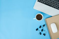 Creative flat lay photo of workspace desk. Top view office desk with laptop, notebooks and coffee cup on blue color background. Minimal work space - Creative stock photos