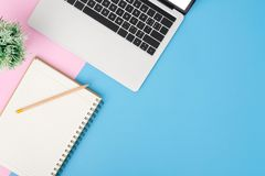 Creative flat lay photo of workspace desk. Top view office desk with laptop, pencil, notebook and plant on blue pink color royalty free stock image