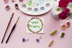 Creative flat lay of watercolor palette, bouquet of flowers, paint brushes, card with words. Good morning written in calligraphy style with floral wreath frame Stock Photos