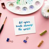 Creative flat lay of watercolor palette, paint brushes, card with inspirational quote. Let your smile change the world written in calligraphy style on a pale Royalty Free Stock Image