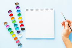 Creative flat lay of watercolor palettes, notebook, female hand holding paint brush. Artist workplace on a blue pastel background stock photo