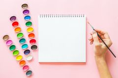 Creative flat lay of watercolor palettes, notebook, female hand holding paint brush. Artist workplace on a pink pastel background. Creative flat lay of stock photos