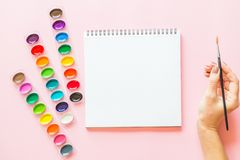 Creative flat lay of watercolor palettes, notebook, female hand holding paint brush. Artist workplace on a pink pastel. Creative flat lay of watercolor palettes stock images