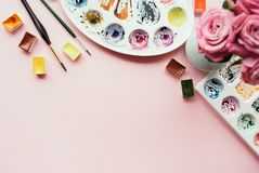Creative flat lay of watercolor palettes, paint brushes, bouquet of pink roses. Artist workplace on a pink pastel background. Stock Photo