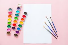 Creative flat lay of watercolor palettes, paint brushes, white paper. Artist workplace on a pink pastel background. Creative flat lay of watercolor palettes stock photos