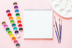 Creative flat lay of watercolor palettes, paint brushes, white paper. Artist workplace on a pink pastel background. Creative flat lay of watercolor palettes stock images