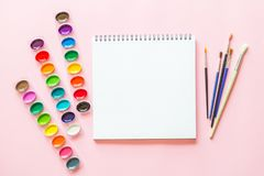 Creative flat lay of watercolor palettes, paint brushes, white paper. Artist workplace on a pink pastel background. Creative flat lay of watercolor palettes royalty free stock image
