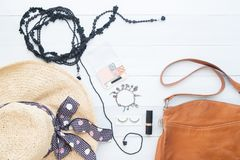 Creative flat lay of woman essentials with leather shoulder bag. On white vintage background Stock Image