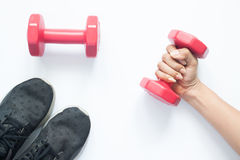 Creative flat lay of woman hand holding red dumbbell Stock Photo