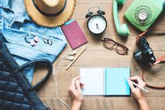 Creative flat lay of woman hands planning trip vacation with accessories. On wooden workspace stock photo