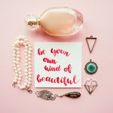Creative flat lay of women`s accessories on a pale pink pastel background. Card with inspirational quote. Be your own kind of beautiful handwritten with Stock Photo