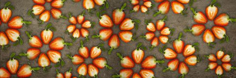 Creative flowers made of strawberries cut from below lit on a stone background Food concept Banner royalty free stock photos
