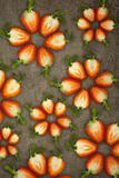 Creative flowers made of strawberries cut from below lit on a stone background Food concept royalty free stock image