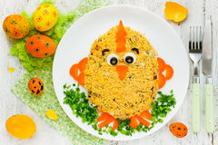 Creative food art idea on Easter meal party for children. Easter salad in the form of cute chicken decorated egg yolk and vegetables stock photo