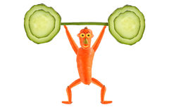 Creative food concept. Funny carrot  raise the bar of cucumber. Royalty Free Stock Photo