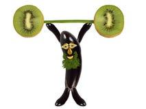 Creative food concept. Funny eggplant raises the bar of kiwi. Royalty Free Stock Photography