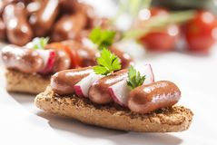 Chicken & Beef cocktail sausage with cherry tomato radish and lemon with green herb with toast bread on green red and bamboo backg. Creative food photography for royalty free stock images
