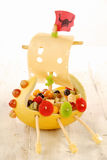 Creative food viking ship for a kids party. Made with fresh fruit salad, vegetables and cheese with a sail, flag, oars and shields down the hull displayed on a Stock Photo