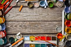 Creative frame from products for drawing and creation. Watercolors, gouache, oil paint, colored pencils, crayons layout on a wooden table. Top view Royalty Free Stock Images