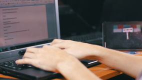 Creative Freelance Designer Working with Laptop. A man working at a laptop sitting at a wooden table on which there are more laptop and tablet with a moving stock video footage
