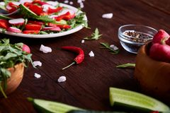 Creative fresh vegetable salad with ruccola, cucumber, tomatoes and raddish on white plate, selective focus. Creative fresh vegetable salad with ruccola Royalty Free Stock Photo