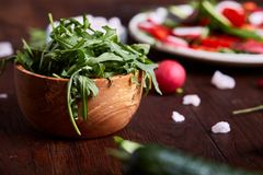 Creative fresh vegetable salad with ruccola, cucumber, tomatoes and raddish on white plate, selective focus. Creative fresh vegetable salad with ruccola Stock Image