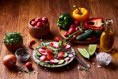 Creative fresh vegetable salad with ruccola, cucumber, tomatoes and raddish on white plate, selective focus. Creative fresh vegetable salad with ruccola Royalty Free Stock Images