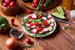 Creative fresh vegetable salad with ruccola, cucumber, tomatoes and raddish on white plate, selective focus. Creative fresh vegetable salad with ruccola Stock Photos