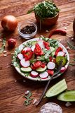 Creative fresh vegetable salad with ruccola, cucumber, tomatoes and raddish on white plate, selective focus. Creative fresh vegetable salad with ruccola Stock Photography