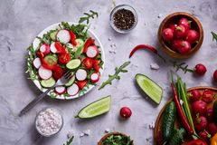 Creative fresh vegetable salad with ruccola, cucumber, tomatoes and raddish on white plate, selective focus. Creative fresh vegetable salad with ruccola Stock Photo
