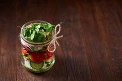Creative vegetable salad served in glass jar over dark wooden background, selective focus, shallow depth of field. Creative fresh vegetable salad served in stock photography