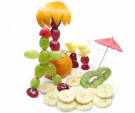Creative fruit child dessert man sunbathing on the beach Royalty Free Stock Images