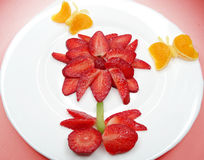 Creative fruit child dessert red flower and butterflies form Stock Images