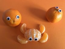 Creative fruit concept, googly eyed oranges. Two googly eyed oranges looking surprised at a peeled orange in the shape of an abstract googly eyed creature royalty free stock photos