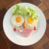 Creative funny breakfast with kid. Creative funny breakfast, top view BLT braakfast on the wooden table with light Stock Images