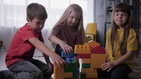 Creative games for children, happy little ones enthusiastically play with a developing constructor build original